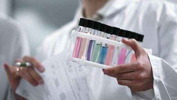 Сотрудник держит пробирки с пробами в Национальной антидопинговой лаборатории