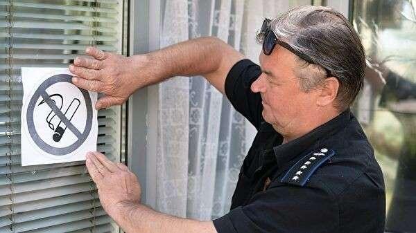 Мужчина размещает запрещающий знак на окне здания на улице города Челябинска