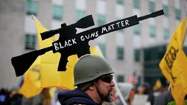 Мужчина с картонной моделью винтовки AR-10 во время акции за ношение оружия в США