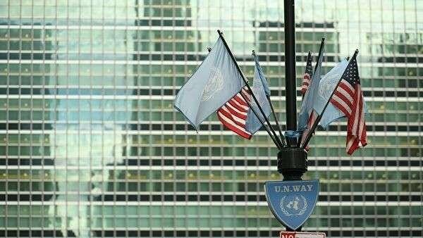 Флаги США и ООН у здания штаб-квартиры ООН в Нью-Йорке