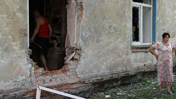Жители Донецка возле дома после обстрела со стороны украинских силовиков