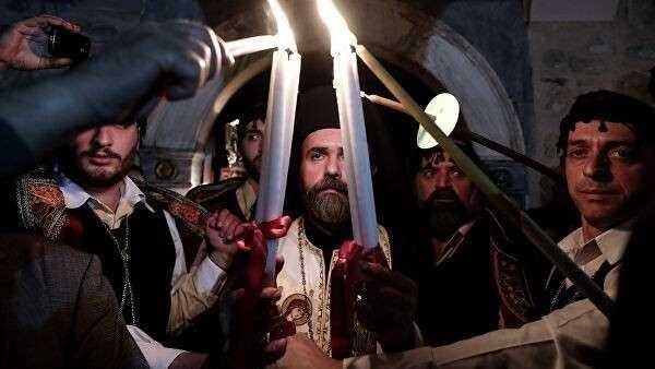 Греческий священнослужитель зажигает свечи верующих Благодатным огнем в церкви в Афинах