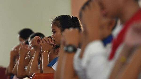 Местные жители во время молебна по погибшим в грузовике в Великобритании в деревне Фу Суан, провинции Нгеан