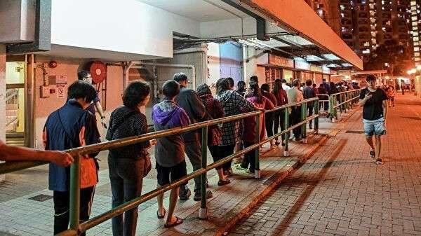 Люди стоят в очереди, чтобы отдать свой голос во время выборов в районный совет в округе Нг Кван О в Гонконге