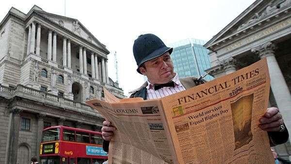 Мужчина читает газету напротив Банка Англии в Лондоне