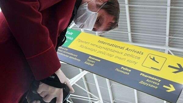 Сотрудник санитарно-карантинного пункта проводит дистанционную термометрию пассажиров, прибывших в аэропорт