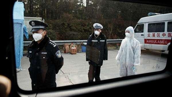 Медицинский работник в защитном костюме и полицейские на контрольно-пропускном пункте в китайской провинции Хунань
