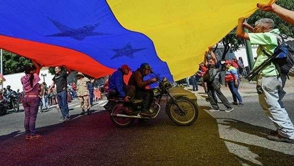 Люди с флагом Венесуэлы в Каракасе