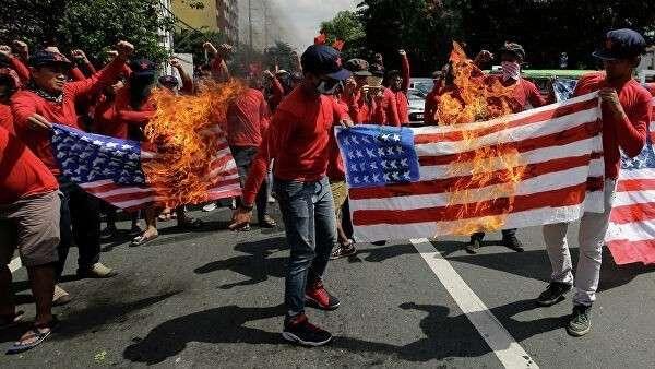 Протестующие жгут флаги США на улице в Маниле, Филиппины