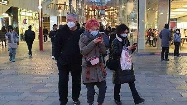 Прохожие в защитных масках на одной из улиц в Пекине