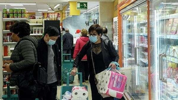 Люди в защитных масках делают покупки в супермаркете в районе Усера в Мадриде. 10 марта 2020