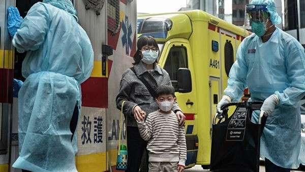 Женщина с ребенок в защитных масках рядом с автомобилем скорой помощи в Гонконге