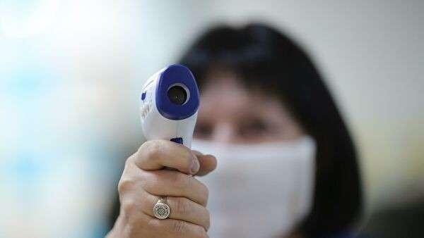 Сотрудница поликлиники  готовится измерять температуру посетителей