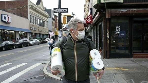Мужчина идет из магазина в защитной маске во время вспышки COVID-19, Нью-Йорк