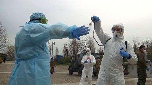 Российские военные специалисты в костюмах бактериологической защиты в лечебном учреждении в Бергамо