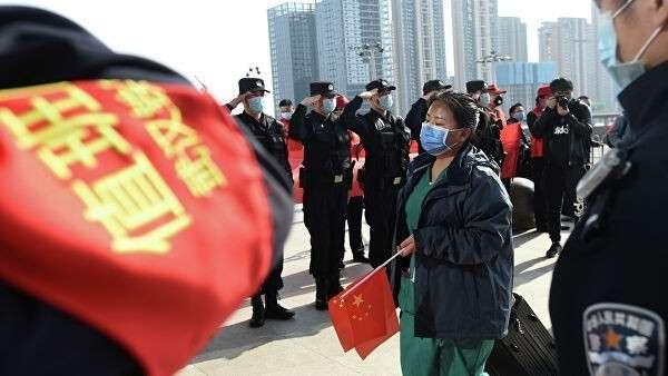 Полицейские приветствуют медицинского работника, покидающего эпицентр вспышки коронавирусной болезни (COVID-19) в провинции Хубэй, Китай