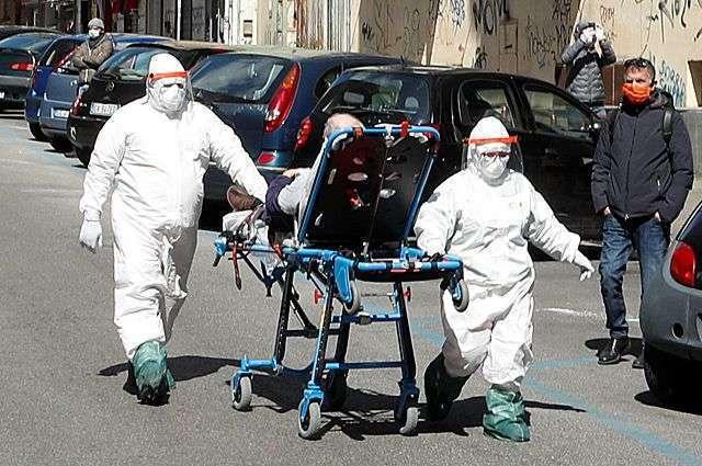 Медперсонал в полном защитном снаряжении перевозит пациента с подозрением на коронавирус по улице Неаполя. Транспортировка на машинах в Италии работает из рук вон плохо.