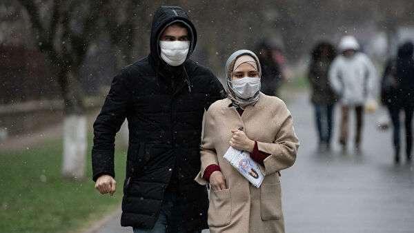 Люди в медицинских масках идут по улице Симферополя