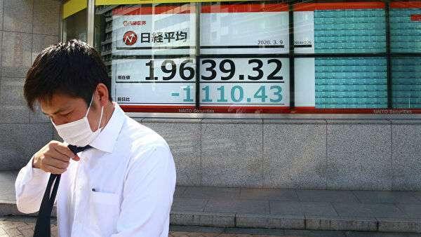 Мужчина в защитной маске на фоне табло с котировками ценных бумаг в Токио, Япония