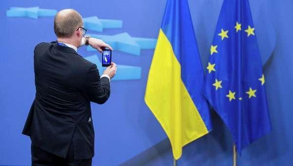 Человек фотографирует флаги Украины и Евросоюза. Архивное фото.