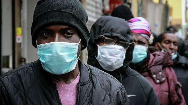 Люди в очереди за масками и едой в районе Гарлема в Нью-Йорке, США