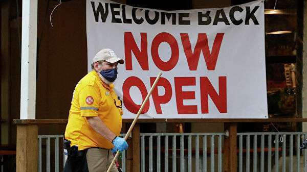 Сотрудник ресторана возле таблички Теперь открыто в Сан-Антонио