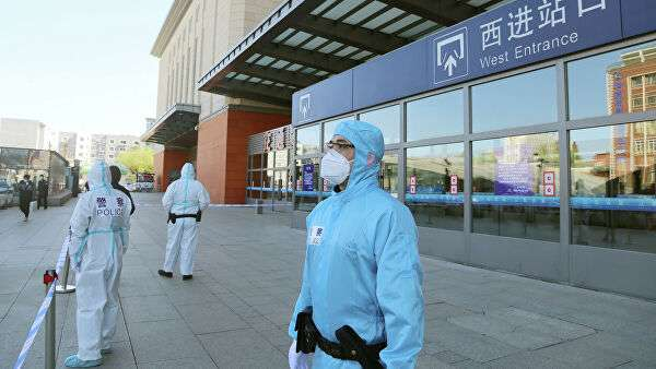Сотрудники полиции в защитных костюмах на закрытой железнодорожной станции в провинции Цзилинь, Китай