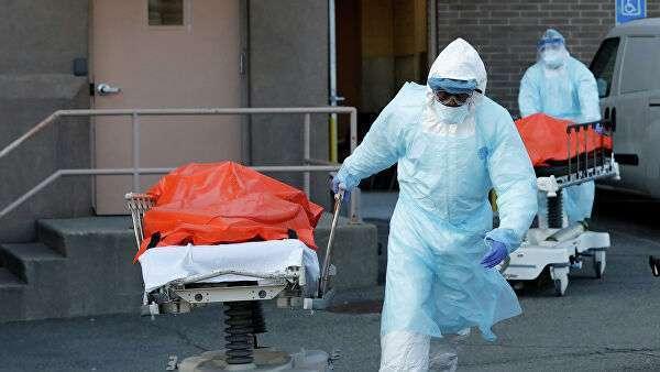 Медицинские работники перевозят тела умерших людей в медицинском центре Wyckoff Heights в Бруклине, Нью-Йорк