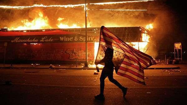 Протестующий несет перевернутый американский флаг возле горящего здания в Миннеаполисе