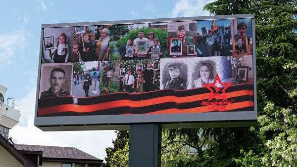Медиаэкран с портретами участников Великой Отечественной войны на Курортном проспекте  в Сочи во время трансляции акции Бессмертный полк онлайн