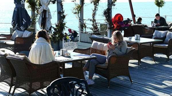 Отдыхающие в кафе на берегу Черного моря в Сочи