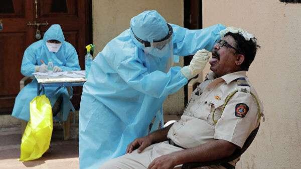 Врач берет мазок на коронавирус в бесплатном медицинском центре в трущобах Дхарави в Мумбаи, Индия
