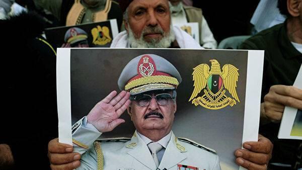 Мужчина держит фото Халифы Хафтара во время демонстрации в Бенгази