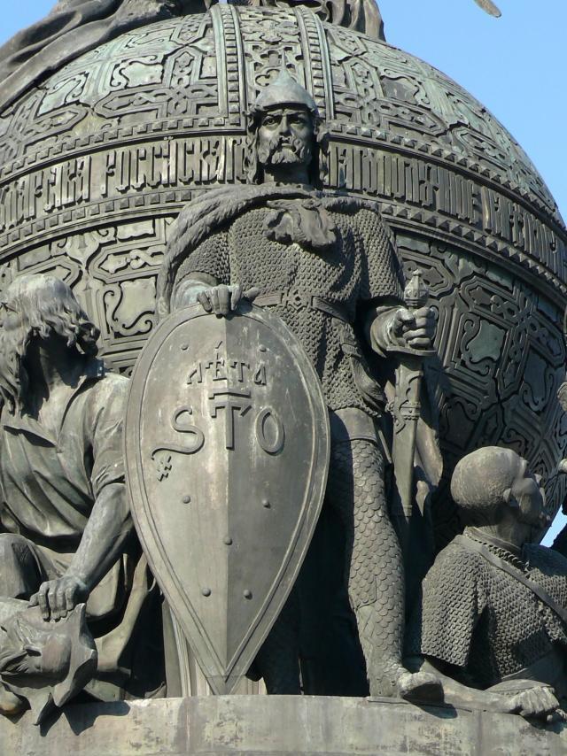 Скульптурная группа «Призвание варягов на Русь» на памятнике «Тысячелетие России» в Великом Новгороде. В центре – первый князь Рюрик в остроконечном шлеме с остроконечным щитом, в звериной шкуре, наброшенной на плечи