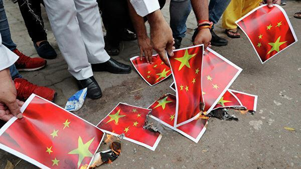 Индийцы сжигают листы бумаги с изображением флага Китая в Лакхнау