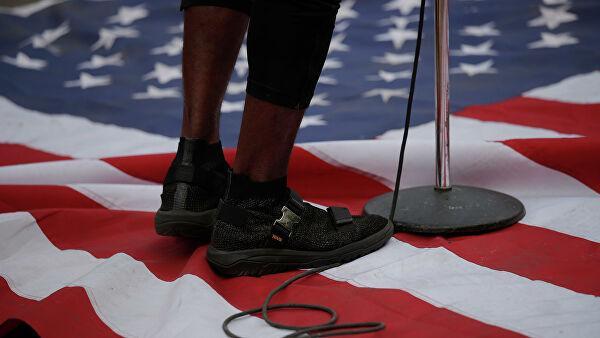 Протестующий стоит на флаге США возле Белого дома