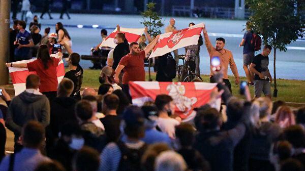 Люди несут старые белорусские национальные флаги во время массовой акции протеста после президентских выборов в Минске, Беларусь. 10 августа 2020