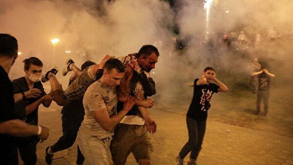 Протестующие несут раненого мужчину во время столкновений с полицией после президентских выборов в Минске, Беларусь. 10 августа 2020