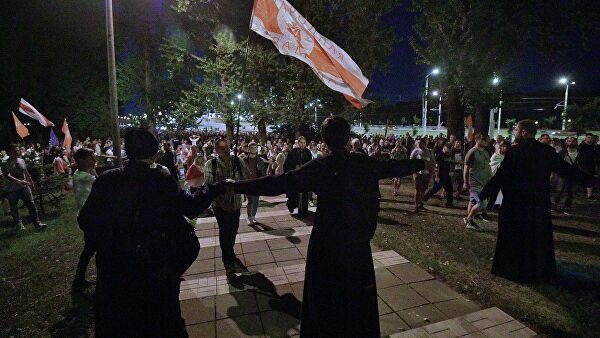 Волонтеры пытаются остановить колонну протестующих, направляющихся к изолятору на улице Окрестина в Минске
